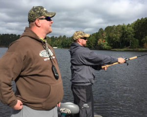 Guide Andy Hendrickson (also a Purple Heart recipient) works with WWIA vet Brian Safford from on his casting technique.
